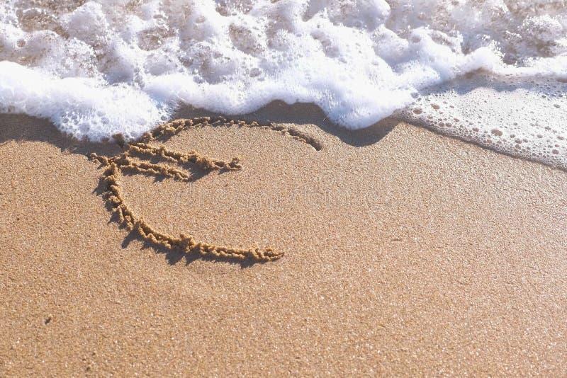 Euro die teken in het overzeese zand wordt geschreven De golven reinigden de inschrijving stock afbeelding