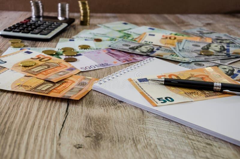 Euro, dolary, monety, notatnik, pi?ro i kalkulator na drewnianym tle zamkni?tym w g?r?, zdjęcia royalty free