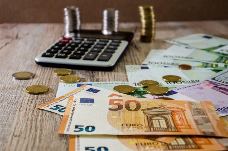 Euro, Dollar, Cents und Taschenrechner verbreiteten heraus auf einem hölzernen Hintergrund lizenzfreies stockbild