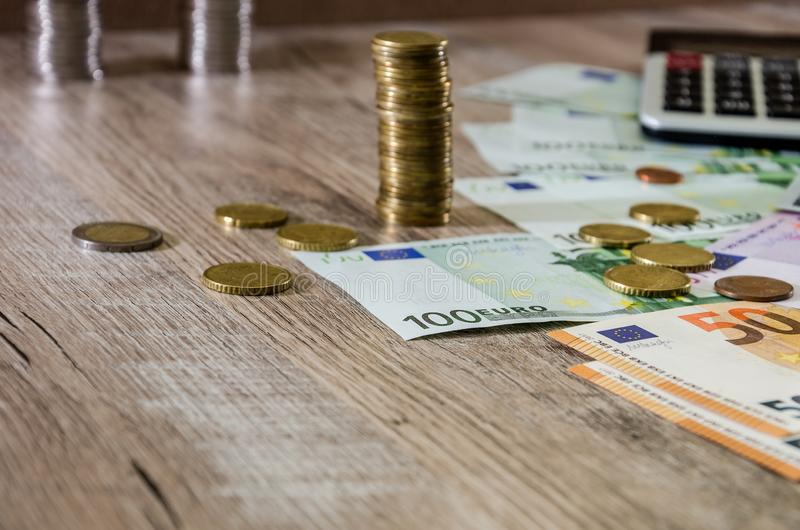 Euro, dollars, cents and calculator spread out on a wooden background. Euro, dollars, cents and calculator royalty free stock photography
