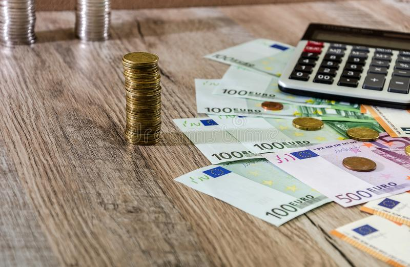 Euro, dollars, cents and calculator spread out on a wooden background royalty free stock photo