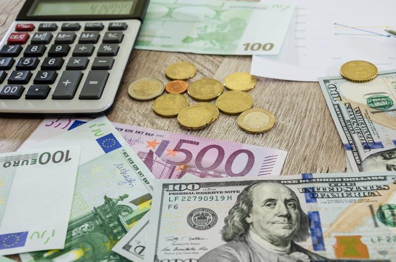 Euro, dollars, muntstukken, calculator en bedrijfsgrafiek op de lijst stock foto