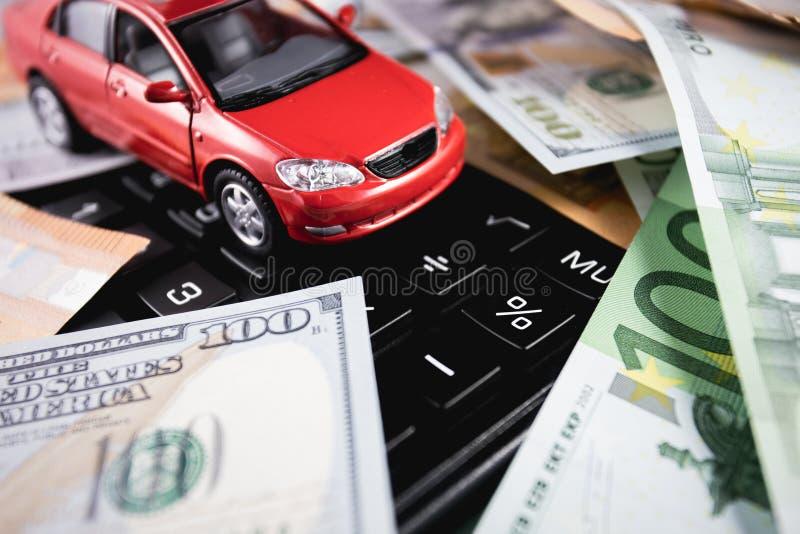 Euro, dollarsbankbiljetten met rode auto op de calculator stock fotografie