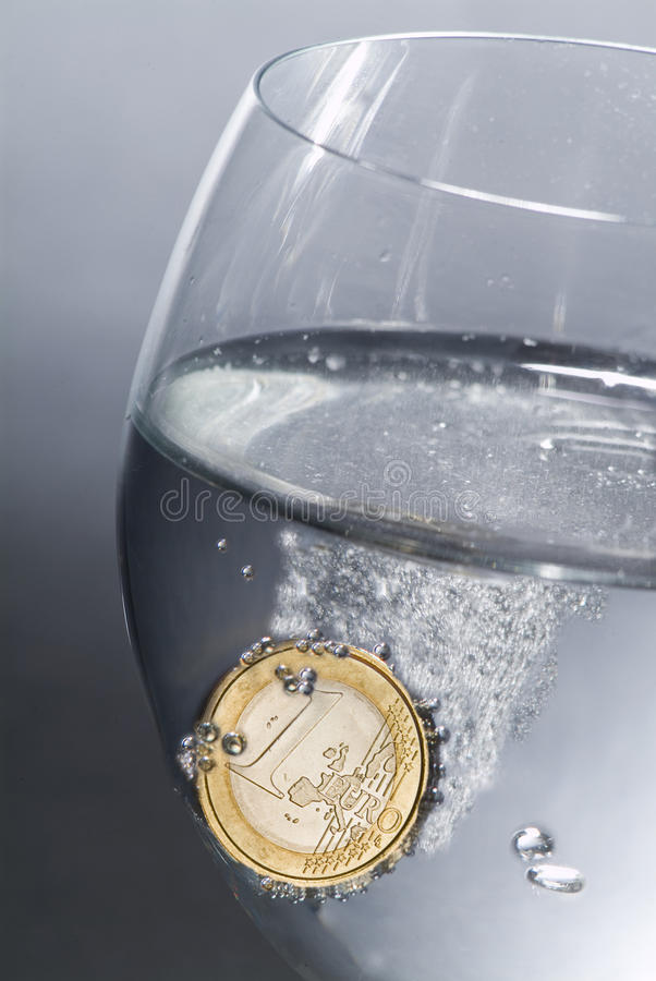 Euro effervescent. A one euro coin in a glass full of water as an effervescent aspirin royalty free stock photography