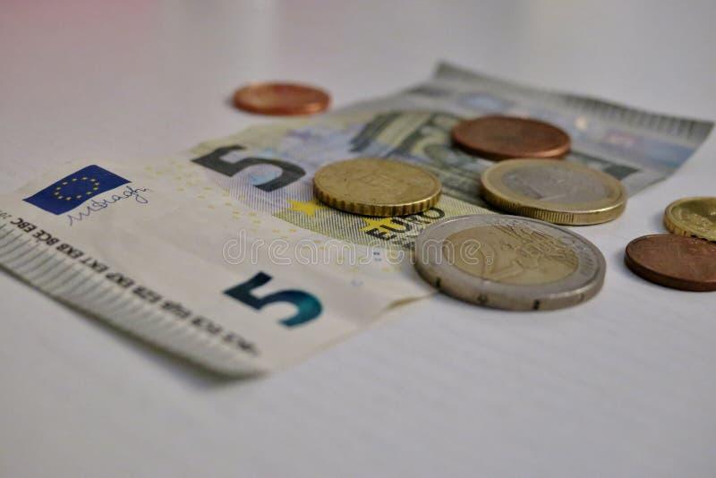 Euro f?nf und ein Penny auf einer wei?en Hintergrundnahaufnahme stockbild