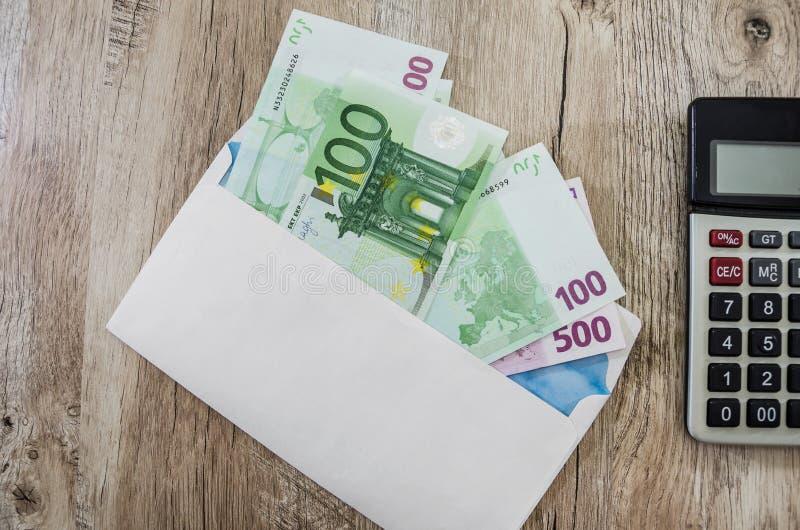 100 euro i ett vit kuvert och del av räknemaskinen på tabellen royaltyfri fotografi