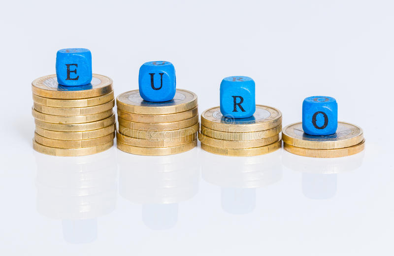 Euro letter cubes with coins against white background stock image