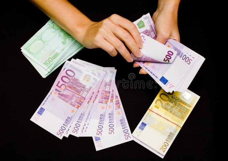 Euro- moeda nas mãos no preto fotos de stock royalty free