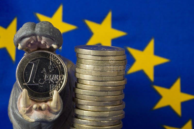 Euro moneta in bocca della figurina dell'ippopotamo, bandiera di UE fotografia stock libera da diritti