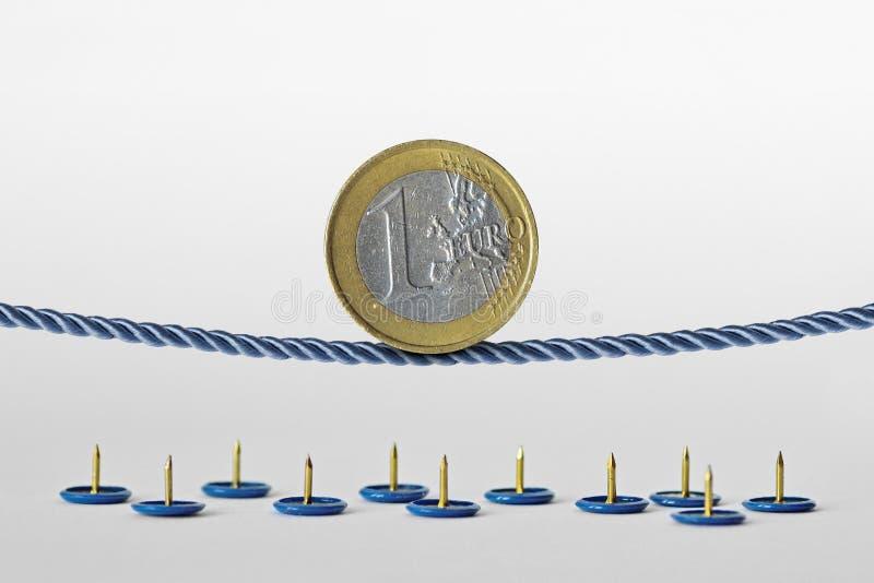Euro moneta che equilibra sulla corda sopra i perni di spinta - concetto di euro rischio di valuta immagine stock libera da diritti
