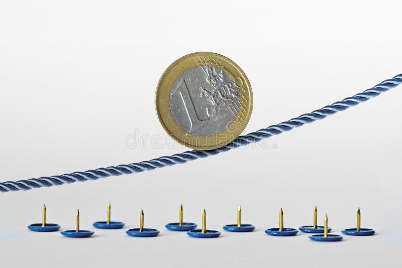 Euro moneta sulla corda sopra i perni di spinta - concetto della tendenza al rialzo di euro valuta e di euro rischio di valuta fotografia stock libera da diritti