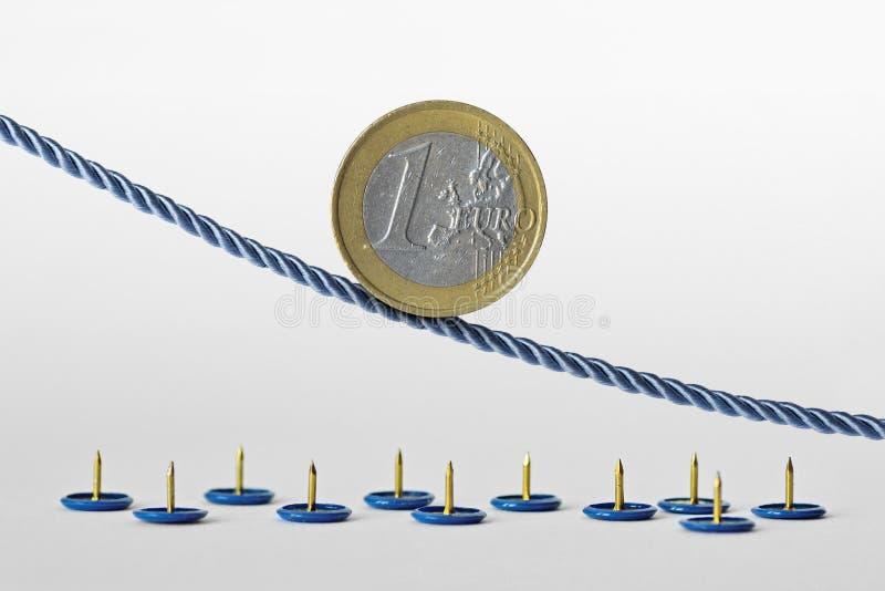 Euro moneta sulla corda sopra i perni di spinta - concetto della tendenza verso il basso di euro valuta e di euro rischio di valu immagini stock