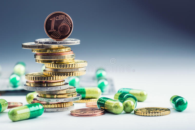 Euro money and medicaments. Euro coins and pills. Coins stacked on each other in different positions and freely pills around. Scattered. Toned image royalty free stock image