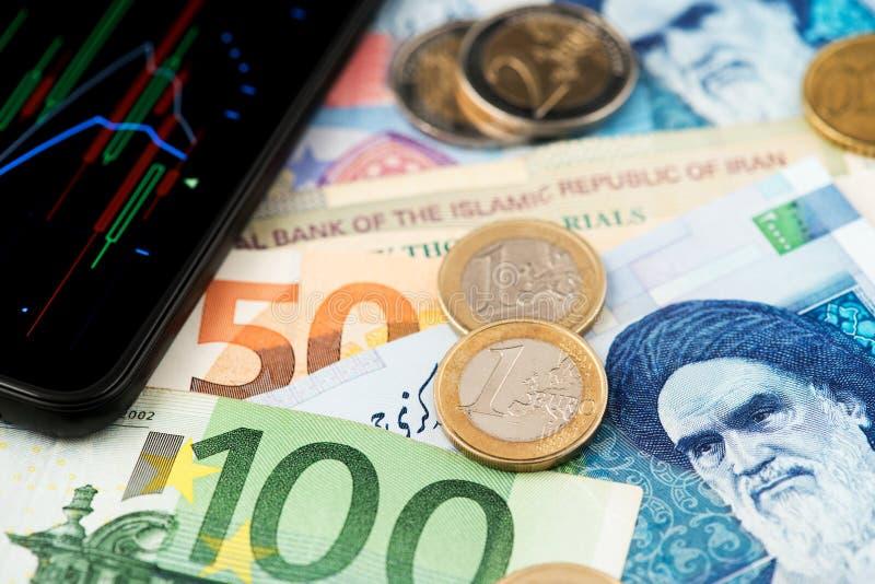 Euro muntstukken en bankbiljetten met Iraanse Rial muntbankbiljetten stock foto's