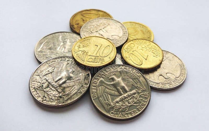 Euro muntstukken en dollarcenten op witte achtergrond stock afbeeldingen