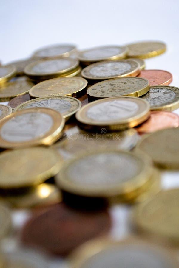 Euro muntstukken van zilveren en goud verspreid op een witte achtergrond stock fotografie