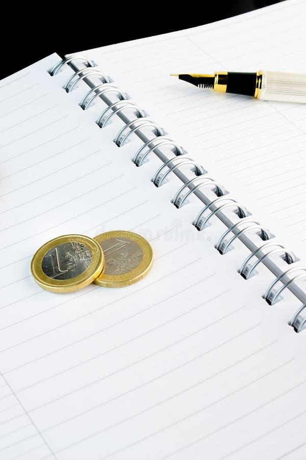 Euro- negócio da moeda no bloco de notas fotografia de stock royalty free