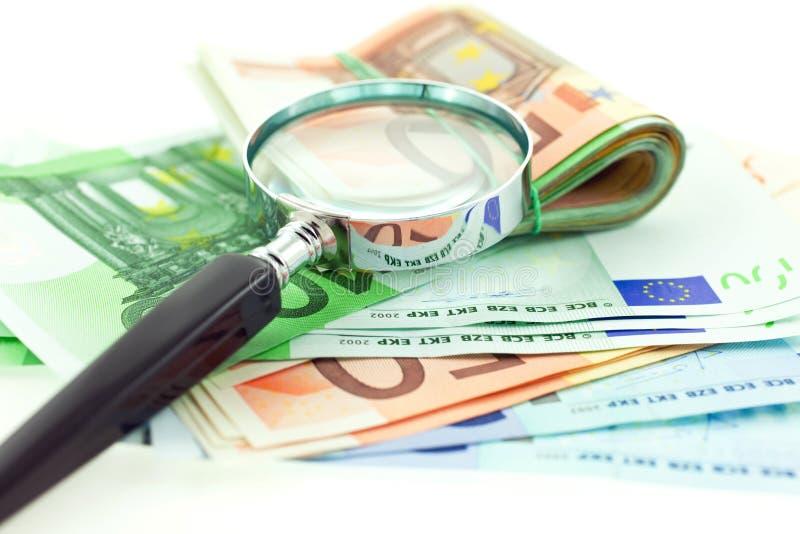 Euro- notas com o magnifier no fundo branco fotografia de stock royalty free