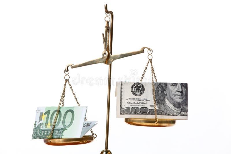 Euro notes et dollar sur des échelles images stock
