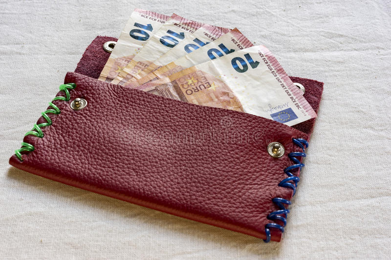 10 Euro notes in an open purse. With colorful stitches on either side lying on a table in a financial concept stock images