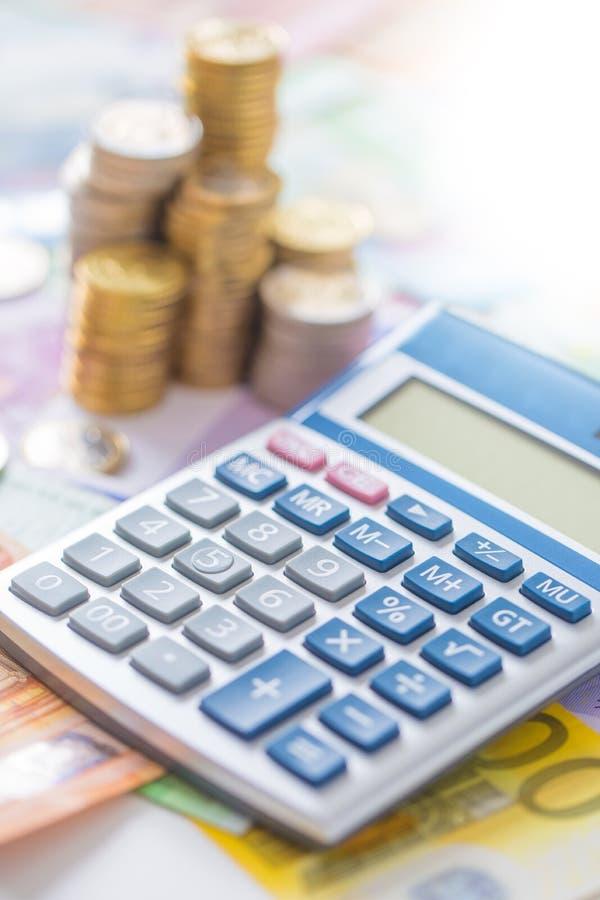 Euro pièces de monnaie en gros plan et billets de banque avec la calculatrice images stock