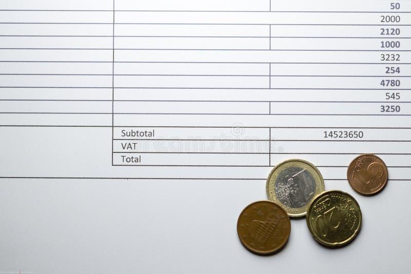Euro pièces de monnaie sur une facture avec la boîte de TVA images stock