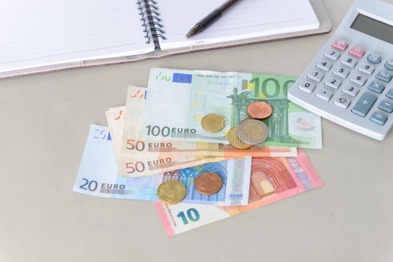 Euro pieniędzy banknoty, monety liczy z i kalkulatorem, notatnikiem i piórem, zdjęcie stock