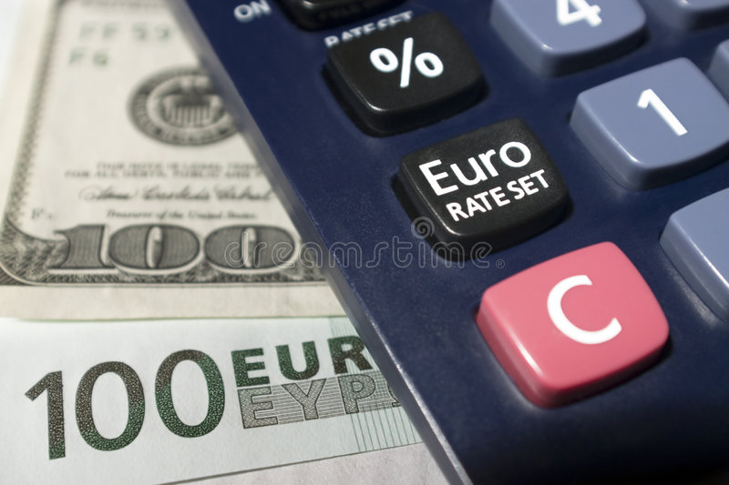 Euro rate set. Part-view of a calculator, Euro rate set button with euro and dollar banknotes as background royalty free stock photo