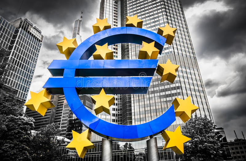 Euro sign at European Central Bank headquarters in Frankfurt, Ge. Rmany with dark dramatic clouds symbolizing a financial crisis royalty free stock images