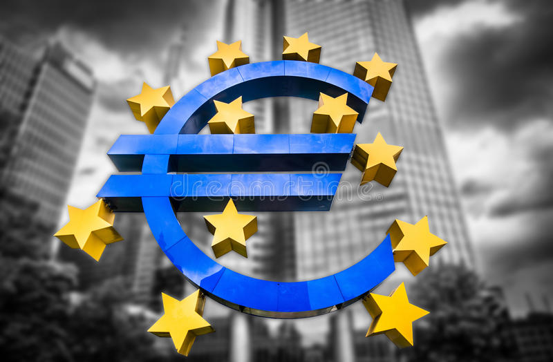 Euro sign at European Central Bank headquarters in Frankfurt, Germany. On abstract blurred background of dark dramatic clouds symbolizing a financial crisis royalty free stock images