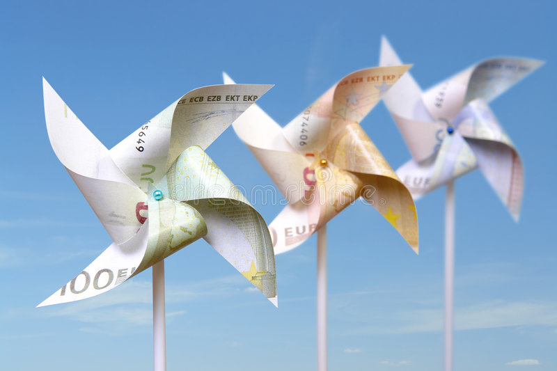 Euro toy windmills. Three toy windmills cut from 100, 50 and 20 euro banknotes over blue sky stock photos