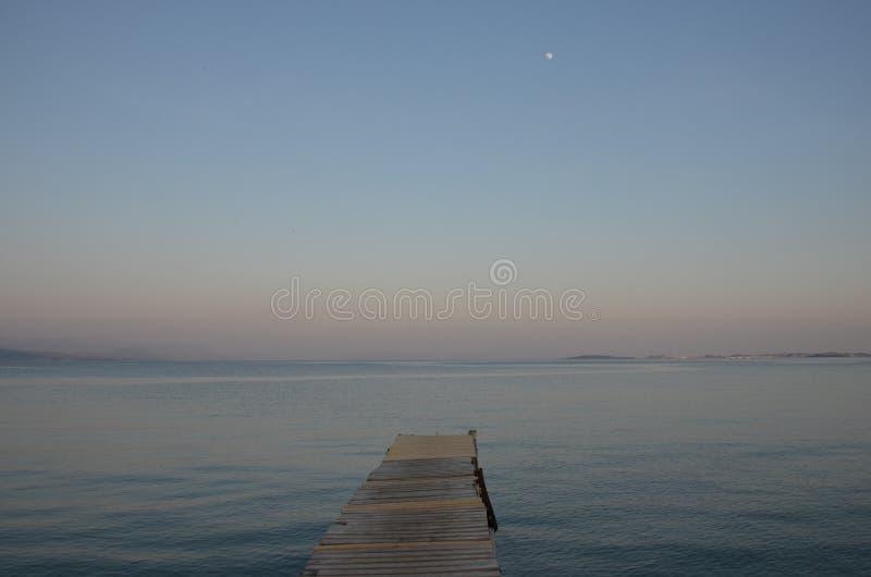 Euro-trip. Greece, Corfu Island. Pierce at dusk. Corfu Island. Old wooden pier on the beach. In May, an amazing calm sea royalty free stock image