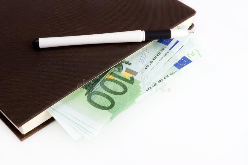 Eurobanknoten, Notizbuch und Stift stockfotografie