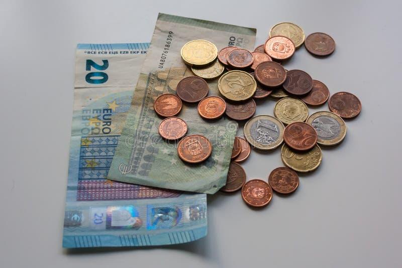 Eurobanknoten und Münzen des schmutzigen Geldes auf weißer Tabelle Dunkles Geschäftskonzept stockfotografie
