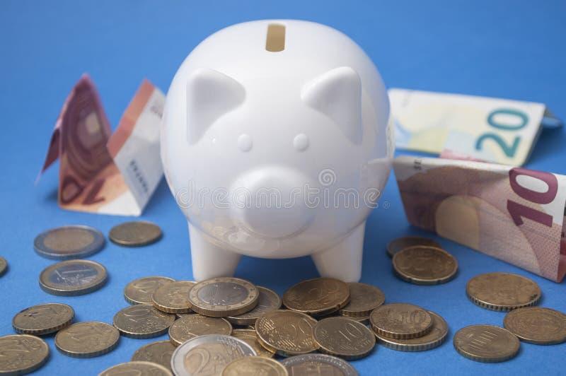 Eurobanknoten und -münzen um ein weißes Sparschwein auf blauem Hintergrund lizenzfreies stockbild