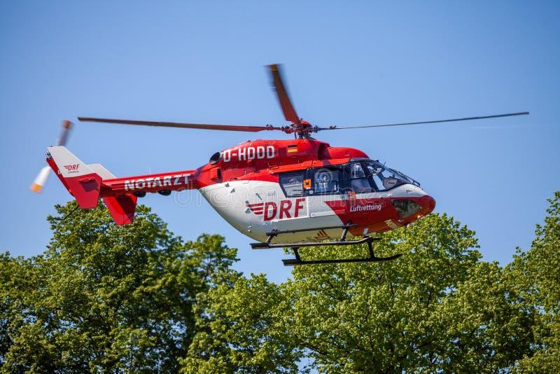 Eurocopter BK-117 de DRF Luftrettung vuela sobre lado del aterrizaje imagenes de archivo