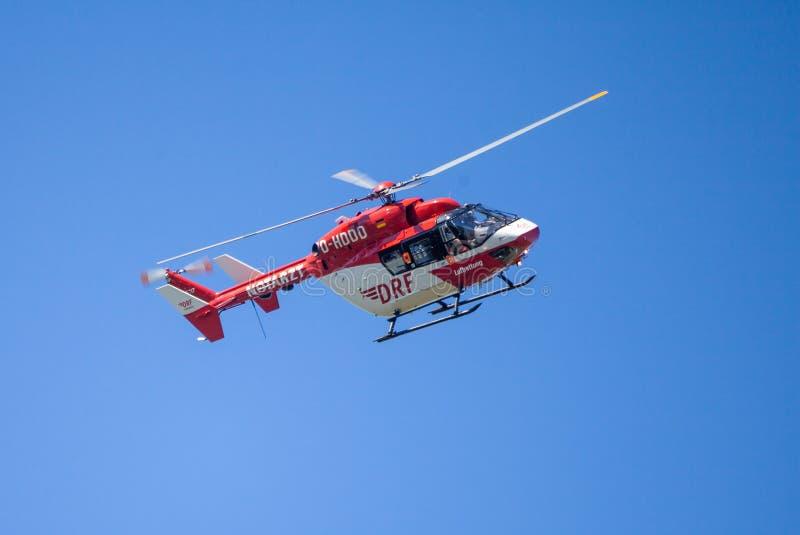 Eurocopter BK-117 von DRF Luftrettung fliegt über Landungsseite stockbilder