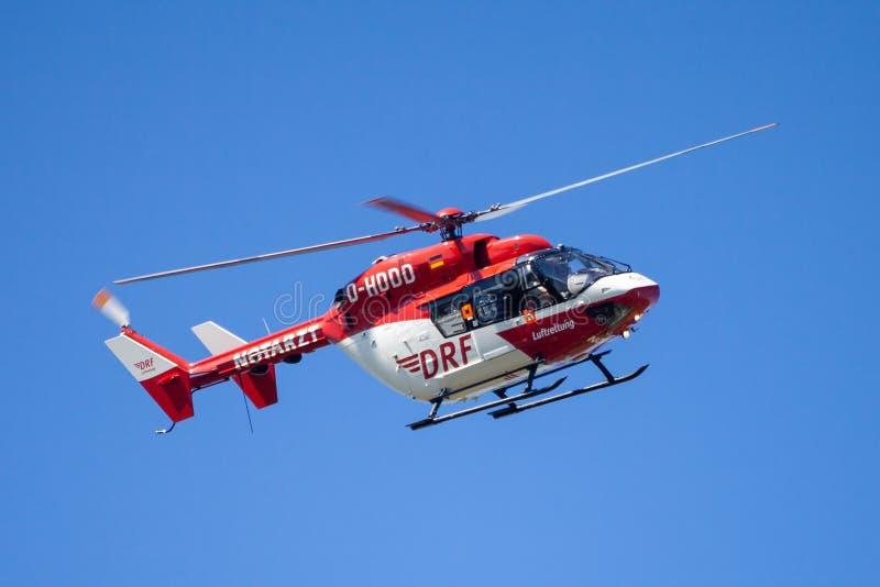 Eurocopter BK-117 von DRF Luftrettung fliegt über Landungsseite lizenzfreies stockfoto
