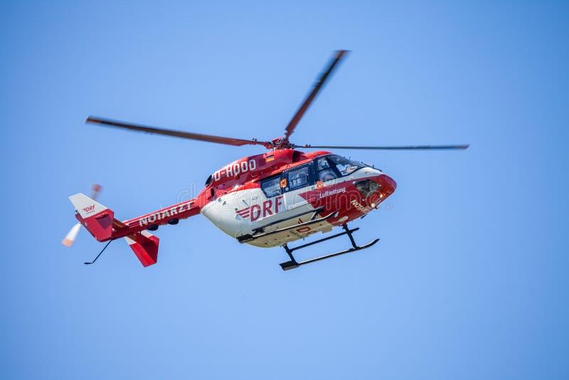 Eurocopter BK-117 von DRF Luftrettung fliegt über Landungsseite lizenzfreie stockbilder