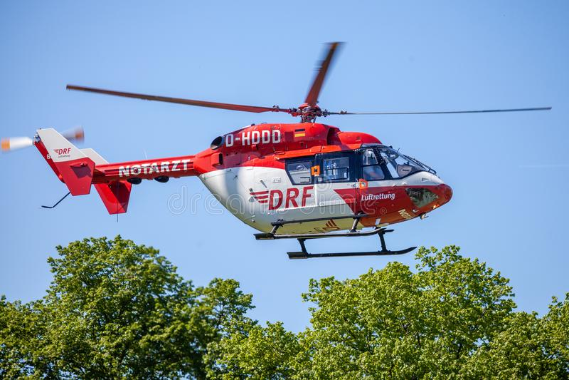 Eurocopter BK-117 von DRF Luftrettung fliegt über Landungsseite stockbild