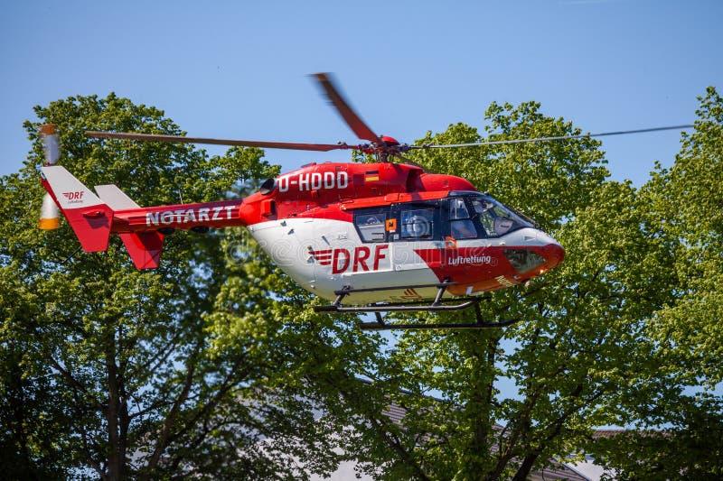Eurocopter BK-117 von DRF Luftrettung fliegt über Landungsseite stockfotos