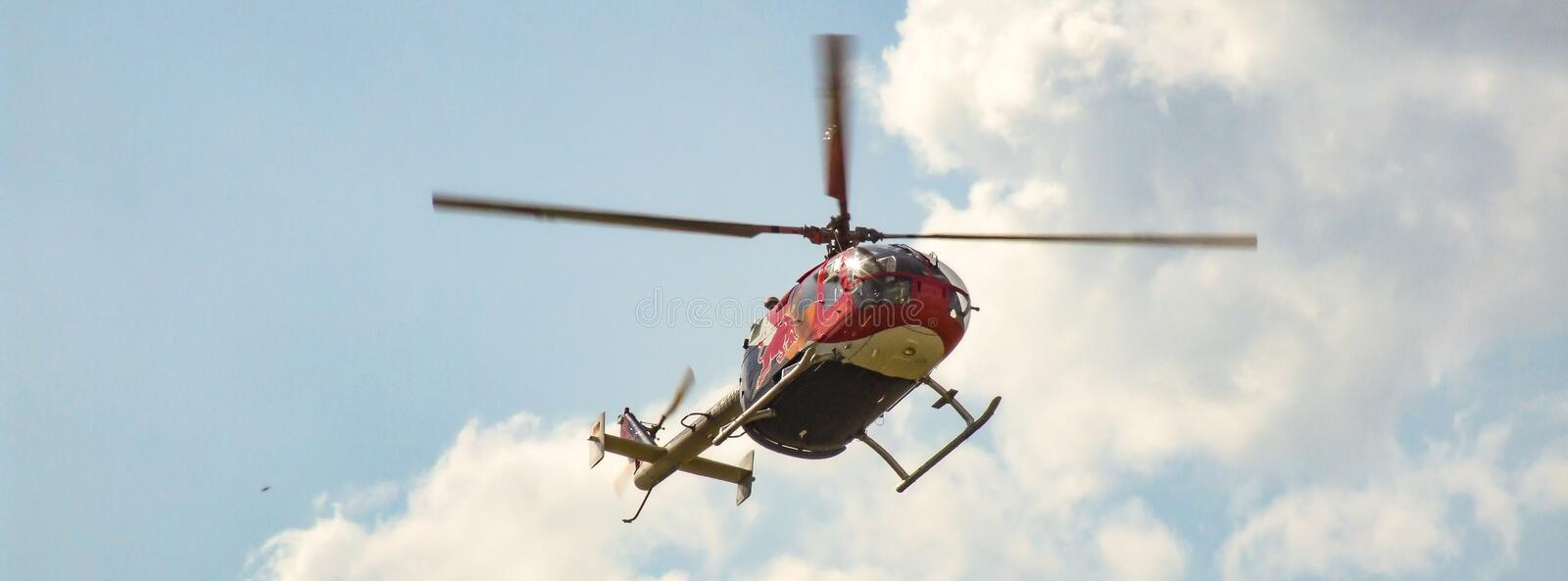 Eurocopter MBB Bo-105 of The Flying Bulls in flight. D-HTDM. Sunny cloudy sky in the background.Photo in facebook background format. Helicopter located in the royalty free stock photography