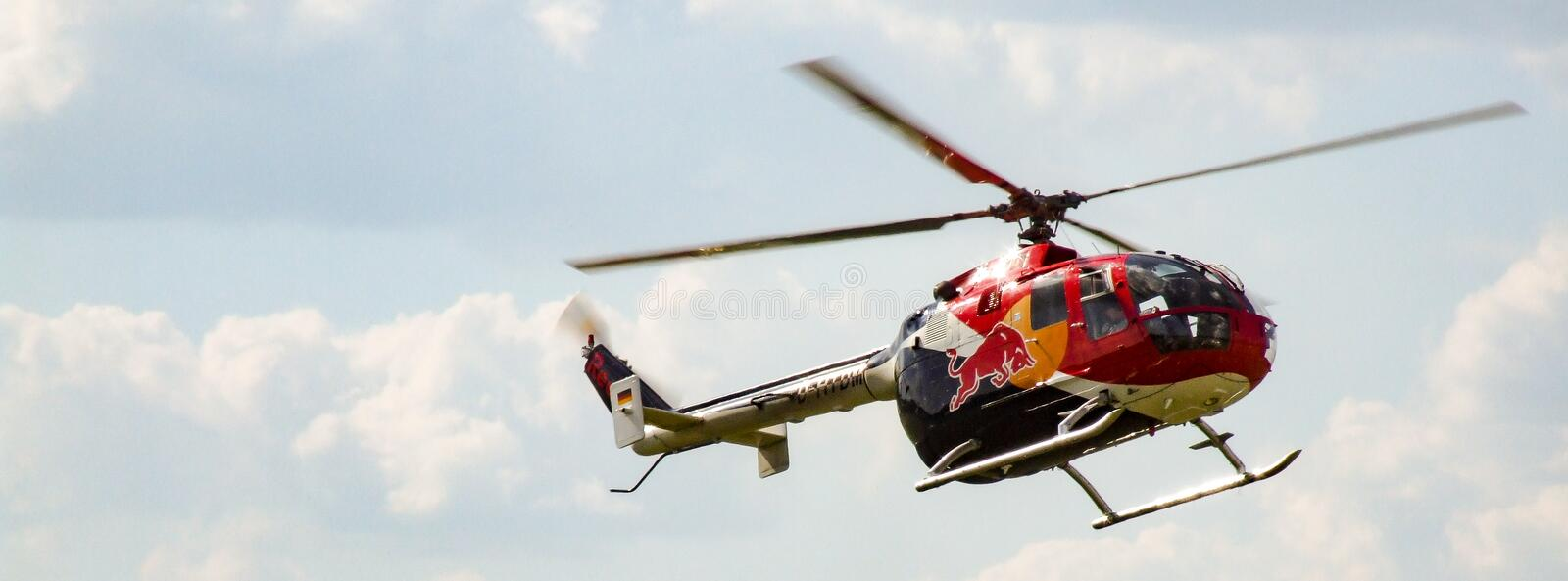 Eurocopter MBB Bo-105 of The Flying Bulls in flight. D-HTDM. Sunny cloudy sky in the background.Photo in facebook background format. Helicopter located in the stock image