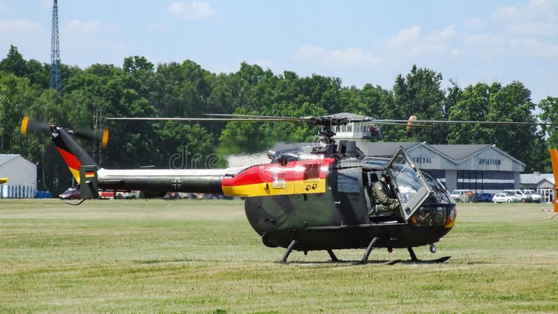 Eurocopter MBB Bo-105 of German Air Force on grass airfield. Eurocopter MBB Bo-105 of German Air Force on grass airfield in Goraszka. Dark gree and black stock images
