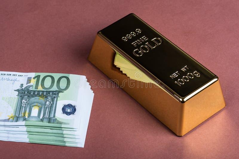 Eurokassa och guld- stång på en brun bakgrund Sedlar pengar bili tacka guldtacka royaltyfri fotografi