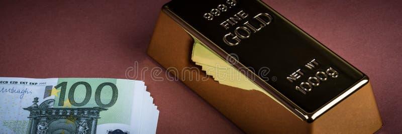 Eurokassa och guld- stång på en brun bakgrund Sedlar pengar bili tacka guldtacka royaltyfri foto