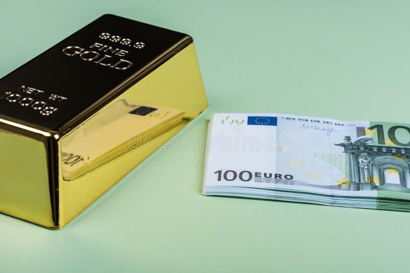 Eurokassa och guld- stång på en grön bakgrund Sedlar pengar bili tacka guldtacka arkivbilder