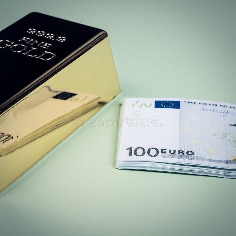 Eurokassa och guld- stång på en grön bakgrund Sedlar pengar bili tacka guldtacka arkivfoton