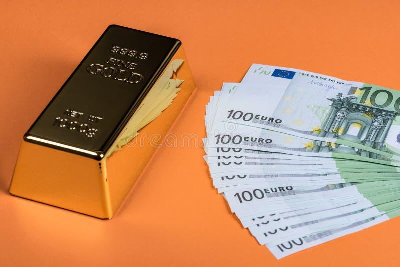 Eurokassa och guld- stång på en orange bakgrund Sedlar pengar bili tacka guldtacka royaltyfria bilder