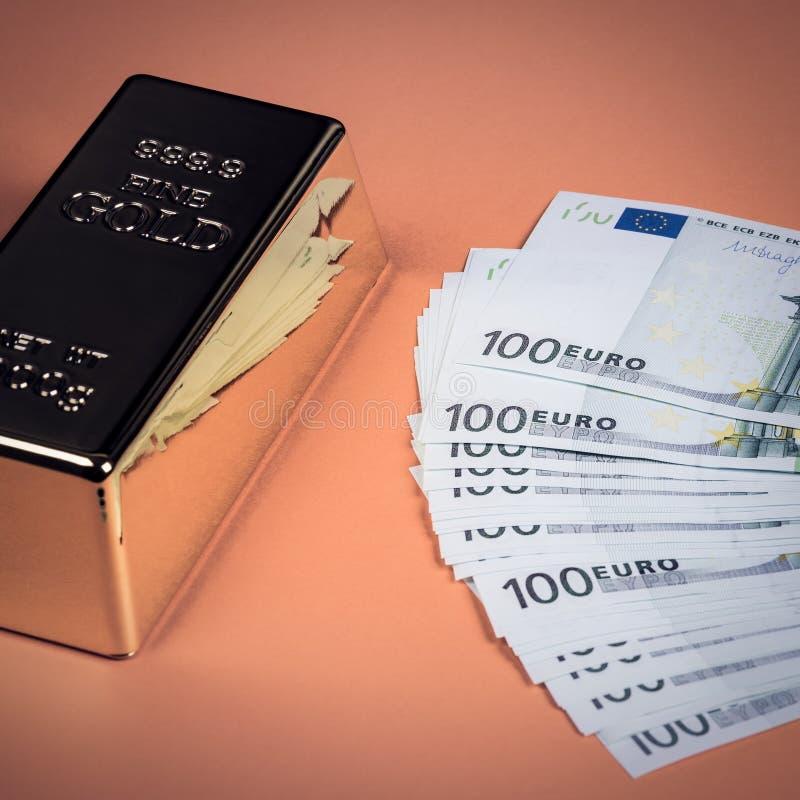 Eurokassa och guld- stång på en orange bakgrund Sedlar pengar bili tacka guldtacka royaltyfri foto